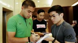 Pemain Timnas Indonesia, Andritany Ardhiyasa, memberikan tanda tangan kepada fans asal Singapura di Hotel Peninsula, Singapura, Jumat (9/11). Indonesia akan melawan Singapura pada laga Piala AFF 2018. (Bola.com/M. Iqbal Ichsan)