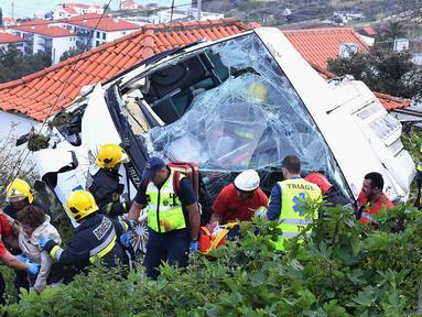 Petugas penyelamat mengevakuasi korban kecelakaan sebuah bus pariwisata di Kota Canico, Pulau Madeira, Portugal, Rabu (17/4). Sebanyak 28 orang yang sebagian besar turis dari Jerman, meninggal dunia, sementara 22 lainnya terluka dalam insiden tersebut. (Rui Silva/Aspress/Global Imagens via AP)