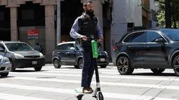 Seorang pria mengendarai skuter bermotor di jalanan di San Francisco (17/4). Pemberhentian operasi skuter bermotor ini karena belum adanya kepastian terhadap keamanan dan keselamatan penggunaan skuter di tempat umum. (AP/Jeff Chiu)