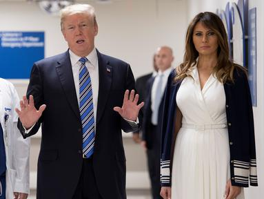 Presiden AS Donald Trump (tengah) didampingi istrinya Melania Trump (kanan) dan dokter Igor Nichiporenko (kiri) saat mengunjungi rumah sakit Broward Health North Pompano Beach, Florida (16/2). (AFP Photo/Jim Watson)