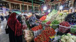 Seorang pembeli mengenakan masker dan sarung tangan lateks, karena pandemi virus corona COVID-19, membeli sayuran selama bulan suci Ramadan di Taheran, Iran (25/4/2020). (AFP/Atta Kenare)