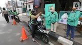 Ojek online (ojol) menerima bantuan berupa bingkisan makan siang dan hand sanitizer di kawasan Jalan Raden Saleh, Jakarta, Selasa (7/3/2020). Bantuan dari DPP PKB guna meringankan beban ojol yang sepi orderan akibat lesunya perekonomian selama pandemi corona Covid-19. (Liputan6.com/Fery Pradolo)