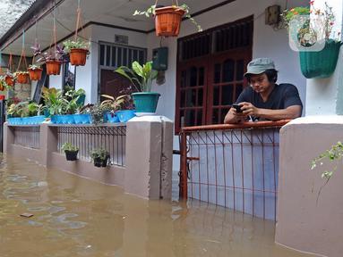 Warga bermain ponsel saat banjir merendam RW 06 kawasan Mekarsari, Depok, Jawa Barat, Sabtu (20/2/2021). Banjir yang disebabkan meluapnya aliran Kali Cipinang Timur ini terjadi akibat intensitas hujan tinggi di wilayah tersebut (Liputan6.com/Herman Zakharia)