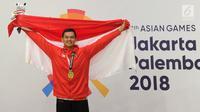 Pesilat Indonesia, Aji Bangkit Pamungkas mengibarkan bendera Merah Putih usai meraih medali emas ke-16 untuk Indonesia dalam babak final Kelas I Putra Asian Games 2018 di TMII, Jakarta, Senin (27/8). (Merdeka.com/Arie Basuki)