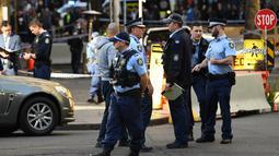 Polisi berjaga di tempat kejadian setelah seorang pria menikam seorang wanita dan berusaha menikam orang lain di pusat kota Sydney (13/8/2019). Polisi mengatakan wanita itu dalam kondisi stabil tidak mengalami luka. (AFP Photo/Saeed Khan)