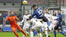 Striker Inter Milan, Lautaro Martinez, melepaskan sundulan ke gawang Spezia pada laga Liga Italia di Stadion Giuseppe Meazza, Minggu (20/12/2020). Inter Milan menang dengan skor 2-1. (AP/Luca Bruno)