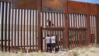 Seorang pemuda berhasil melewati tembok besi perbatasan antara Meksiko dan Amerika Serikat di negara bagian Chihuahua, Meksiko (6/4). Aksi nekat ini dapat ditindak tegas oleh pihak keamanan Amerika Serikat. (AFP/Herika Matinez)
