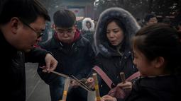 Keluarga membakar dupa untuk berdoa keberuntungan pada hari kelima Tahun Baru Imlek di Yonghegong, atau Kuil Lama di Beijing (9/2). Warga China merayakan Tahun Babi tersebut dengan doa, pesta keluarga, dan belanja. (AFP Photo/Nicolas Asfouri)