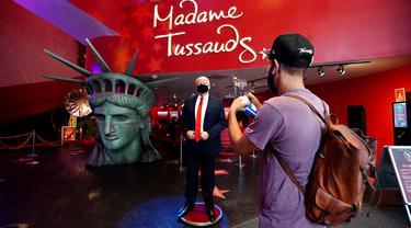 Pengunjung menganbil foto sosok Donald Trump yang bermasker saat Madame Tussauds New York dibuka kembali di New York City, Kamis (27/8/2020). Patung lilin Donald Trump akan berada di pintu masuk untuk mengingatkan tentang protokol kesehatan, termasuk pemakaian masker (Cindy Ord/Getty Images/AFP)