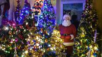 Sosok Santa Claus berdiri di antara pohon-pohon Natal di ruang tamu rumah keluarga Thomas Jeromin di Rinteln, Jerman, Minggu (8/12/2019). Thomas Jeromin memenuhi rumahnya dengan 350 pohon Natal di hampir tiap sudut rumah, mulai dari ruang tamu, dapur sampai kamar mandi. (Ina FASSBENDER/AFP)