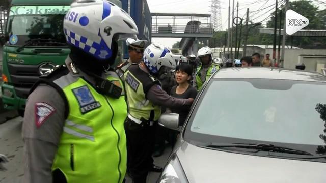 Menghindari razia seorang pengendara mobil nyaris menabrak petugas polisi yang memggelar operasi pajak kendaraan.