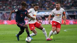 Gelandang Bayern Munchen, Kingsley Coman, berusaha melewati gelandang RB Leipzig, Christopher Nkunku, pada laga Bundesliga 2019/20 di Leipzig, Sabtu (14/9). Kedua klub bermain imbang 1-1. (AFP/John Macdougall)