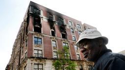 Penghuni apartemen yang terbakar memeriksa lokasi kejadian di kawasan Harlem, New York, AS, Rabu (8/5/2019). Keenam korban tewas yang masih satu keluarga diketahui bernama Andrea Pollidore (45), Mac Abdularaulph (33), Nakiyra (11), Andre (8), Brooklyn (6), dan Ellijah (4). (AP Photo/Richard Drew)
