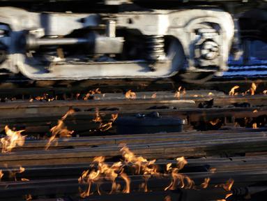 Sistem pemanas berbahan bakar gas menghangatkan lintasan rel kereta di dekat stasiun Metra Western Avenue, Chicago, 29 Januari 2019. Para petugas berupaya membuat kereta komuter tetap beroperasi di tengah suhu udara yang sangat dingin. (AP/Kiichiro Sato)
