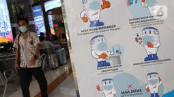 Papan sosialisasi pencegahan penularan virus COVID-19 di Stasiun Gambir, Jakarta, Rabu (16/12/2020). 47 KA jarak jauh yang dioperasikan selama masa Nataru 2020/2021 terdiri dari, 22 KA dari Stasiun Gambir, 23 dari Stasiun Pasar Senen, dan dua dari Jakarta Kota. (Liputan6.com/Helmi Fithriansyah)