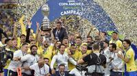 Para pemain dan official Brasil merayakan gelar juara Copa America 2019 setelah mengalahkan Peru pada laga final di Stadion Maracana, Rio de Janeiro, Minggu (7/7). Brasil menang 3-1 atas Peru. (AFP/Carl De Souza)