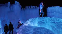 Manajer situs Tim Bauman mengenakan crampon saat dia naik ke atas salah satu air mancur es untuk membuat para tamu terkagum-kagum di Kastil Es di Excelsior, Minnesota (18/1). (Anthony Souffle/Star Tribune via AP)