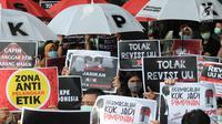 Pegawai KPK membawa poster saat menggelar aksi di Lobi Gedung KPK, Kuningan, Jakarta, Jumat (6/9/2019). Dalam aksi menolak revisi UU KPK tersebut, mereka mengenakan baju serba hitam lengkap dengan masker penutup mulut dan memasang KPK Lines di sekitar pintu masuk. (merdeka.com/Dwi Narwoko)