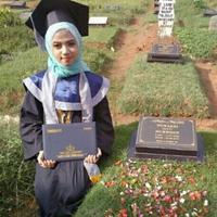 Inilah kisah di balik foto gadis cantik berhijab yang mengenakan pakaian wisuda sambil membawa ijazah duduk disamping kuburan. (Foto: Instagram/@imaspermata)