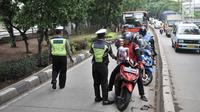 Polisi memberhentikan pengendara yang melintasi jalur bus Transjakarta di Jalan Yos Sudarso, Jakarta, Senin (21/1). Razia ini sekaligus meningkatkan kedisiplinan dalam berkendara. (Merdeka.com/Iqbl Nugroho)