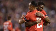 Pemain Liverpool, Kolo Toure, berpelukan dengan rekannya Nathaniel Clyne usai menaklukan Bordeaux pada laga Liga Europa di Stadion Anfield, Inggris, Kamis (26/11/2015). Liverpool berhasil menang 2-1. (AFP Photo/Oli Scarff)