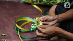 Pedagang menjalin pita untuk membuat pernak-pernik ketupat hias di Pasar Asemka, Jakarta, Selasa (4/5/2021). Pedagang mulai menjual pernak-pernik menjelang Lebaran seperti ketupat hias dengan harga mulai dari Rp15.000 hingga Rp60.000 tergantung ukuran. (Liputan6.com/Faizal Fanani)