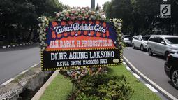 Karangan bunga ucapan duka cita dari Agung Laksono untuk Probosutedjo dipajang di Jalan Diponegoro, Jakarta, Senin (26/3). Probosutedjo merupakan pengusaha yang juga pendiri Himpunan Pengusaha Pribumi Indonesia (Hippi). (Liputan6.com/Arya Manggala)
