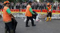 Petugas PPSU membersihkan sampah sisa perayaan Hari Buruh Internasional di kawasan Silang Barat Daya Monas, Jakarta, Rabu (1/5). Sampah yang berserakan di kawasan tersebut membuat Petugas PPSU bekerja ekstra keras untuk membersihkan kawasan tersebut. (Liputan6.com/Helmi Fithriansyah)