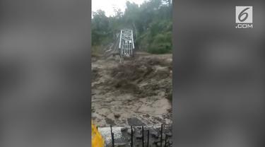 Banjir bandang di Brebes membuat sebuah jembatan ambruk. Kendaraan yang parkir juga ikut tersapu oleh arus banjir.