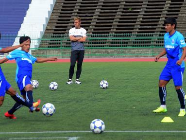 Gelandang Jepang, Keisuke Honda (tengah) menyaksikan pemain timnas Kamboja berlatih di Stadion Olimpiade Nasional di Phnom Penh, (4/9). Federasi Sepak Bola Kamboja (FFC) mengontrak Honda menjadi pelatih berdurasi dua tahun. (AFP Photo/Tang Chhin Sothy)