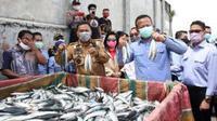 Prabowo bersama Gubernur Sulut Olly Dondokambey berpose dengan memegang sekaligus mengangkat ikan malalugis di Tempat Pelelangan Ikan (TPI) Tumumpa, Manado.