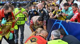 Cristiano Ronaldo yang menyadari tendangan yang dilepaskan mengenai seorang petugas keamanan langsung mendatangi sang petugas dan memberikan uluran tangan padanya. (Foto: AFP/Fabrice Coffrini)