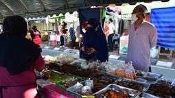 Orang-orang mengenakan masker saat membeli makanan di pasar menjelang berbuka puasa selama bulan suci Ramadan di Provinsi Narathiwat, Thailand, Selasa (5/5/2020). Ramadan kali ini berlangsung di tengah bayang-bayang virus corona COVID-19. (Madaree TOHLALA/AFP)