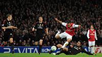 Pemain Arsenal, Theo Walcott menghindari tekel pemain AC Milan pada laga Liga Champions di Stadion Emirates, Selasa (6/3/2015). Kecepatan Walcott kerap merepotkan barisan pertahanan lawan. (AFP Photo/Adrian Dennis)