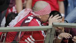 Pentolan suporter PSM Makassar, Daeng Uki, berusaha menenangkan anaknya yang menangis saat PSM Makassar takluk dari Persija Jakarta pada laga final Piala Indonesia di SUGBK, Minggu (21/7). Persija menang 1-0 atas PSM.  (Bola.com/M Iqbal Ichsan)