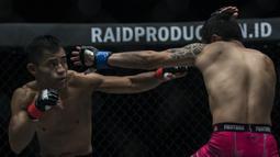 Atlet MMA Indonesia, Stefer Rahardian, tukar pukulan dengan atlet MMA China, Peng Xue Wen, pada kelas strawweight di JCC Senayan, Jakarta, Sabtu (22/9/2018). Stefer Rahardian kalah dari Peng Xue Wen. (Bola.com/Vitalis Yogi Trisna)