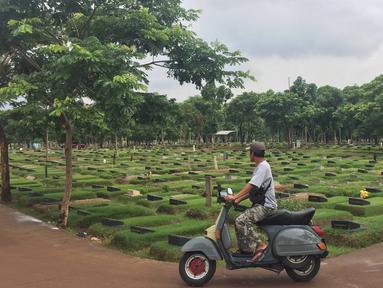 Pengendara sepeda motor melintas di sekitar TPU Pondok Ranggon, Cipayung, Jakarta, Sabtu (28/12/2019). Pengelola TPU Pondok Ranggon mulai memberlakukan tumpang jasad dalam satu liang lahat jelang habisnya masa tampung pada Januari 2020. (Liputan6.com/Immanuel Antonius)