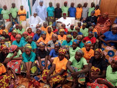 Presiden Nigeria Muhammadu Buhari (tengah) duduk di antara 82 gadis Chibok yang berhasil dibebaskan dari Boko Haram di Presidential Villa di Abuja, Nigeria (7/5). (AFP Photo/PGDBA&HND Mass Communication)