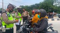 Pemeriksaan warga yang melewati penyekatan PPKM level 4 Pekanbaru oleh polisi. (Liputan6.com/M Syukur)