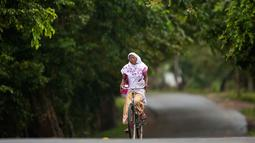 Seorang wanita asal Assam mengenakan pakaian tradisional mengendarai sepeda di Kaziranga, India, (11/10). Daerah ini terkenal dengan Taman Nasional Kaziranga. (AP Photo/Anupam Nath)