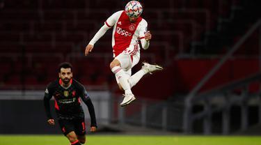 Bek Ajax Amsterdam, Nicolas Tagliafico mengontrol bola diawasi penyerang Liverpool, Mohamed Salah pada pertandingan pertama Grup D Liga Champions 2020 di Johan Cruijff Arena, Kamis (22/10/2020) dini hari WIB. Liverpool susah payah menang tipis 1-0 di kandang Ajax. (AP Photo/Peter Dejong)