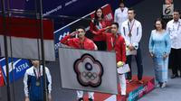 Pebulu tangkis Indonesia, Jonatan Christie dan Anthony Ginting memberi hormat saat menyanyikan lagu Indonesia Raya saat usai upacara penghargaan cabang olahraga badminton Asian Games 2018 di Jakarta, Selasa (28/8). (Liputan6.com/Helmi Fithriansyah)