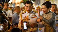 Raja Thailand Maha Vajiralongkorn dan Ratu Suthida menyapa pendukungnya di luar Grand Palace di Bangkok setelah memimpin upacara keagamaan di sebuah kuil Buddha di dalam Istana Raja pada Minggu (1/11/2020). (Lillian SUWANRUMPHA / AFP)