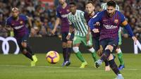 Lionel Messi mencetak gol untuk Barcelona melalui tendangan penalti pada laga melawan Real Betis. (AFP/Josep Lago)
