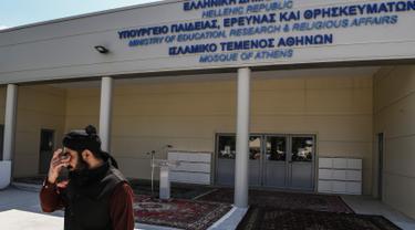 Seorang Muslim berdiri di luar bangunan masjid resmi pertama di Kota Athena, Yunani pada Jumat (7/6/2019). Masjid tersebut akan siap digunakan untuk beribadah puluhan ribu umat Muslim di Athena setelah melalui proses pembangunan selama lebih dari satu dekade. (Aris MESSINIS / AFP)
