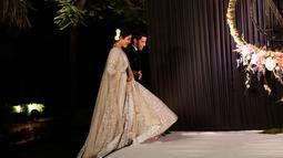 Aktris Bollywood Priyanka Chopra dan musisi AS Nick Jonas berjalan saat resepsi pernikahan mereka di New Delhi, India, Selasa (4/12). Priyanka Chopra dan Nick Jonas menikah dalam dua upacara yang berbeda. (AP Photo/Altaf Qadri)
