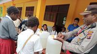 Bhabinkamtibmas ajarkan pola cuci tangan yang baik kepada pelajar. (Liputan6.com/Katharina Janur/Polda Papua)