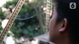 Teknisi sedang menyambungkan film sebelum pertunjukkan layar tancap di kawasan Sawangan, Depok, Jawa Barat, Sabtu (11/7/2020). Layar tancap atau bioskop terbuka menjadi alternatif bagi warga untuk menikmati film di tengah penerapan new normal di kawasan Jabodetabek. (Liputan6.com/Herman Zakharia)