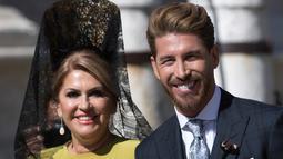 Bek Real Madrid, Sergio Ramos bersama ibunya tersenyum saat tiba di gereja dalam upacara pernikahannya di Sevilla, Spanyol  (15/6/2019). Ramos resmi menikahi kekasihnya Pilar Rubio setelah berpacaran sejak 2012. (AP Photo/Antonio Pizarro)