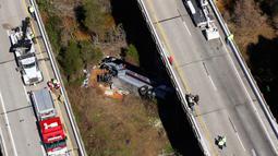 Petugas penyelamat mengevakuasi bangkai bus carteran yang kecelakaan di Loxley, Alabama (13/3). Dilaporkan sopir dari bus ini meninggal, dan puluhan penumpang mengalami luka berat. (AP Photo / Dan Anderson)